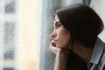 אישה מביטה מהחלון בעצב